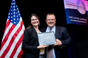 enator Jon Tester (MT) presenting the Community Development award to Courtney McKee of Headframe Spirits in Butte, MT.
